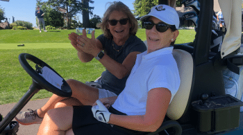 two women in golf cart smiling and clapping