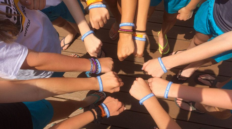 Camp Canadensis campers with hands in circle and SCOPE bracelets