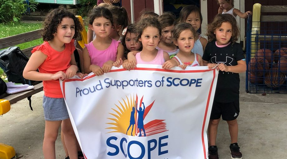 Pierce Country Day Camp girls holding a SCOPE sign