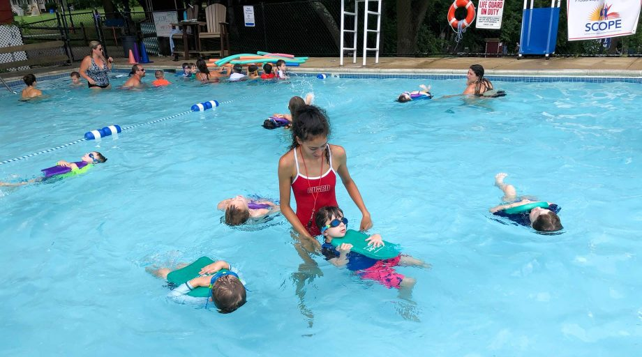 swim instructor teaching kids how to swim