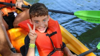 YCMA camper giving peace sign while kayaking