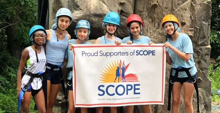 Campers climbing and holding SCOPE sign