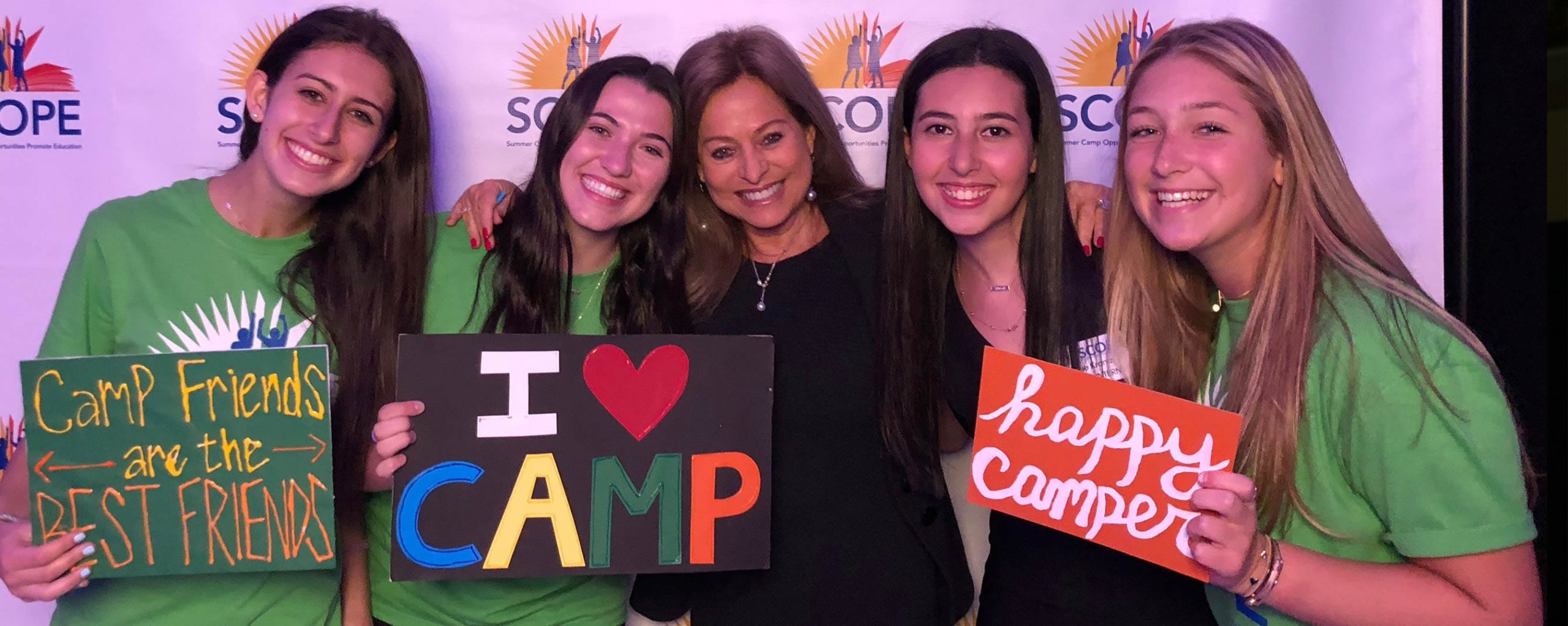 "Campers from SCOPE holding up ""Happy Camper"" signs"