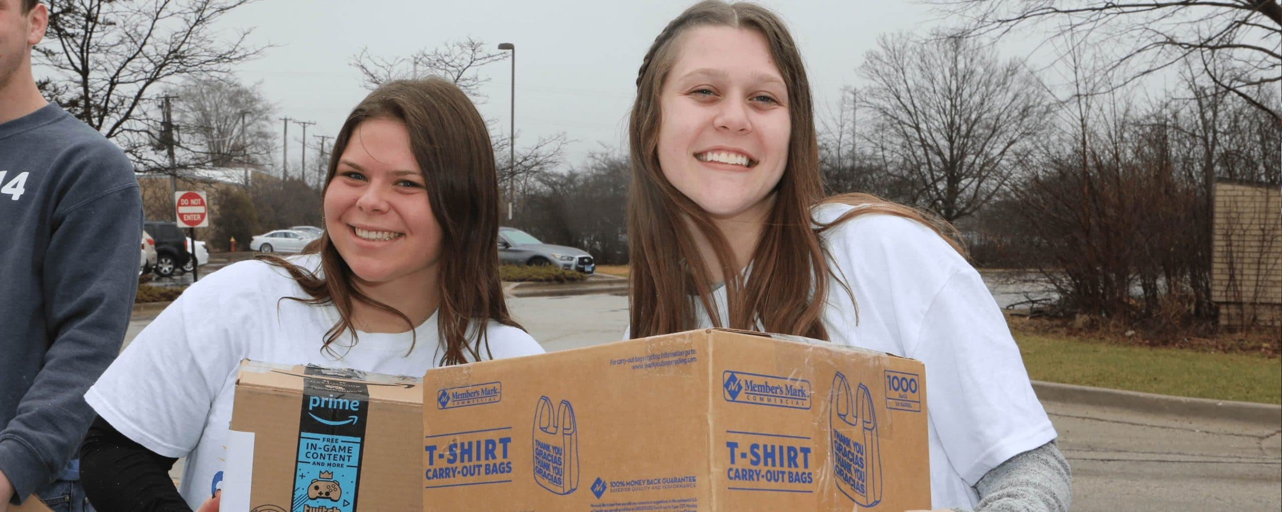two girls holding boxes