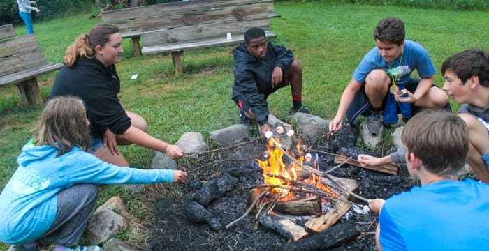 kids toasting marshmallow at camp