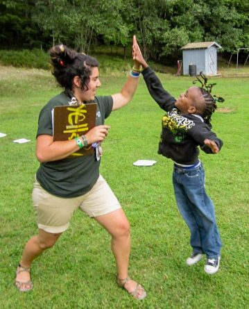 camp counselor giving kid high five