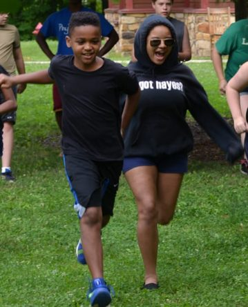 boy and girl running on field at camp