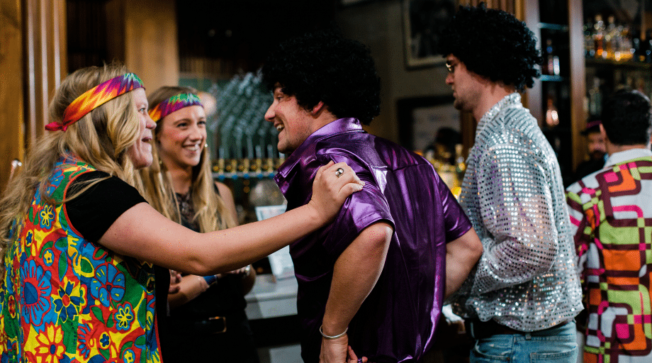 men and women conversing while dressed as hippies